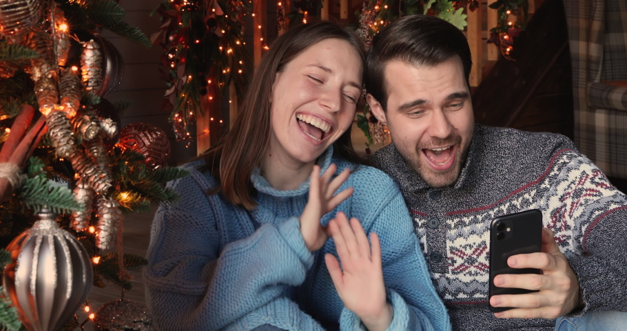 Cherry young couple using smart phone talking to family congratulates Merry Christmas by video call conference app. Modern technology easy and comfort usage, New 2021 Year congrats remotely concept Royalty-Free Stock Footage #1061165395