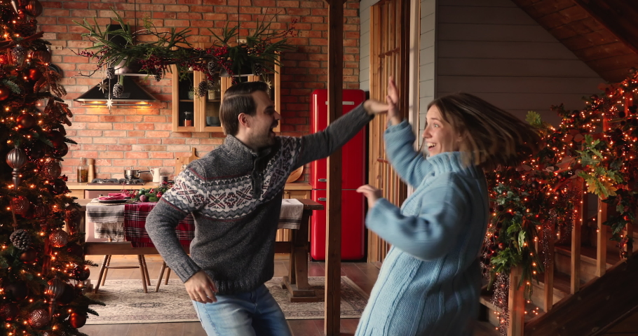 Happy young active couple in winter sweaters enjoy Christmas Eve and 2021 New Year winter holidays dancing indoor at ornate twinkle lights xmas tree home hall. Fun and hobby, x-mas celebration concept Royalty-Free Stock Footage #1061165419