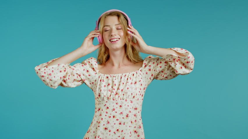 Pretty girl with blonde hair listening to music, smiling, dancing in headphones in studio against blue background. Woman in sexy floral dress. Music, dance, radio concept