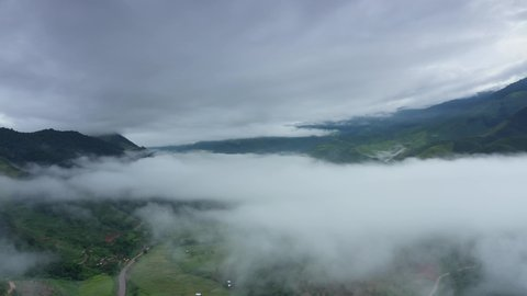 Aerial view over valley surrounded by mountains and covered with dense ground fog and mist High peaks wonderful morning sunrise natural Landscape. Sapan village, nan province, Thailand. 4k resolution