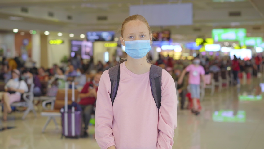 A young woman wearing a medical face mask in an airport stands in a hall and looks into the camera. The concept of the New normal of people's lifestyle. Air travel in the age of Covid-19 | Shutterstock HD Video #1061173435
