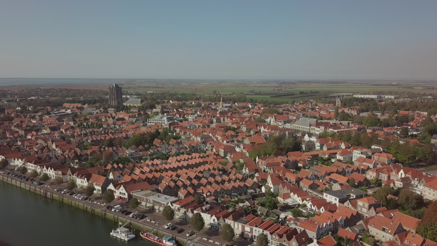 Flight sideways over the town of Zierikzee in the south of Netherlands with red roofs and canals with ships. Sunny cloudless weather with a slightly lower sun. | Shutterstock HD Video #1061174215