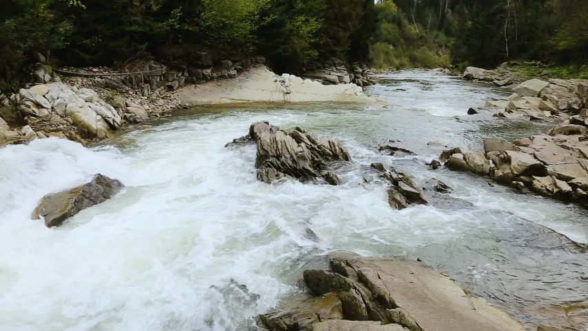 Fast mountain river in the Carpathians. Mountain rapids and gullies. Waterfall on a mountain river. Crystal mountain water.  | Shutterstock HD Video #1061178868