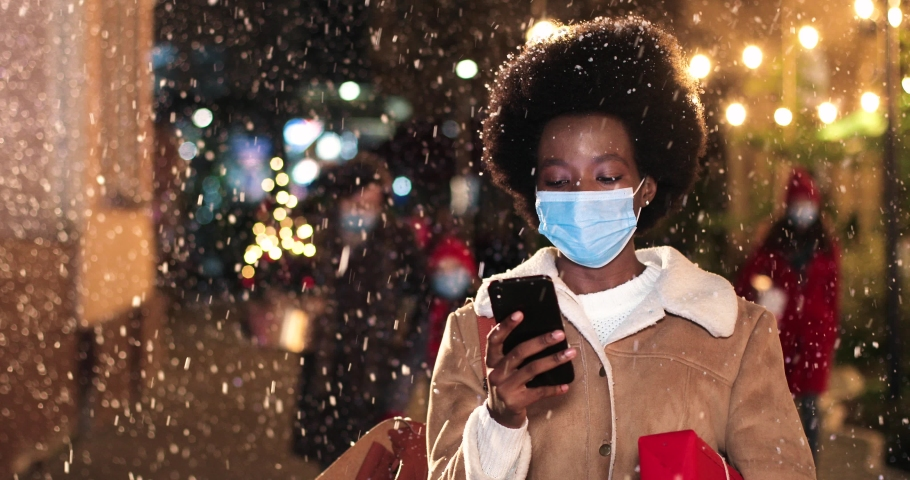 Close up portrait of African American beautiful female in mask browsing on smartphone while standing on crowded snowy street. Young woman with christmas present texting on cellphone. Winter concept