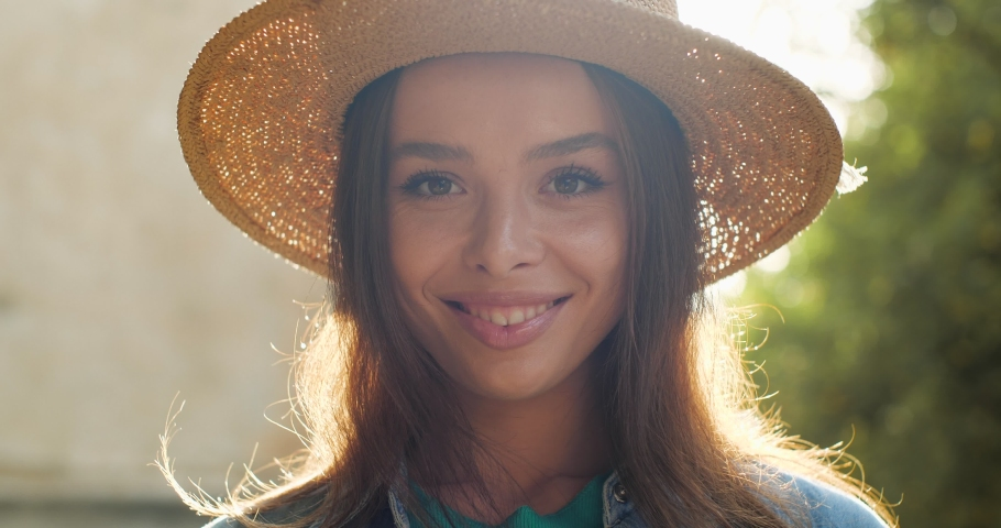 Close Up Portrait of Latino American Female Charmingly smiling at the Camera. Stylish young Girl is posing to the Camera on a sunny warmly Day, wearing trendy Hat. People. Women. Natural Beauty.