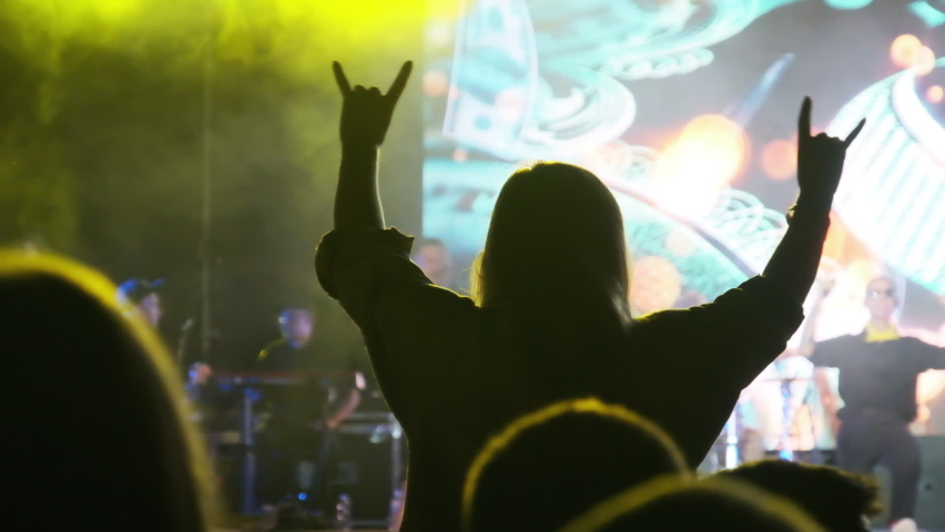 Silhouette of Woman in a Crowd at Rock Concert Showing Sign - Devil's Horns Gesture. Group of people partying, cheering, and raising hands up near Stage. Crowd of Fans having fun at party. Slow Motion