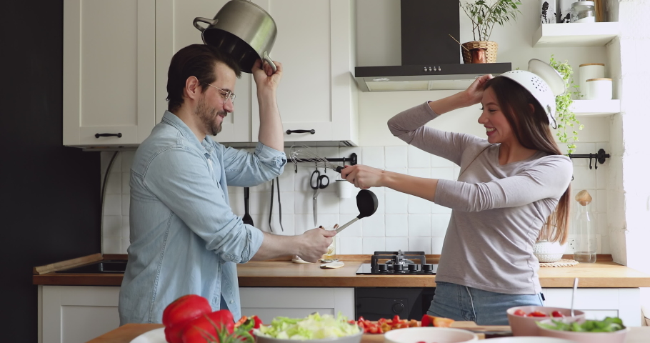 Overjoyed young family couple using kitchen ware utensils as helmets and swords playing fight battle in kitchen, happy spouses involved in childish activity, having fun spending weekend leisure time.