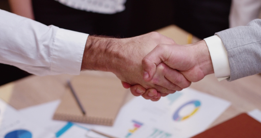 Close up of two men shaking hands. The two businessmen reached agreement and confirmed it with gesture.Slow motion. Team ritual. Agreement.