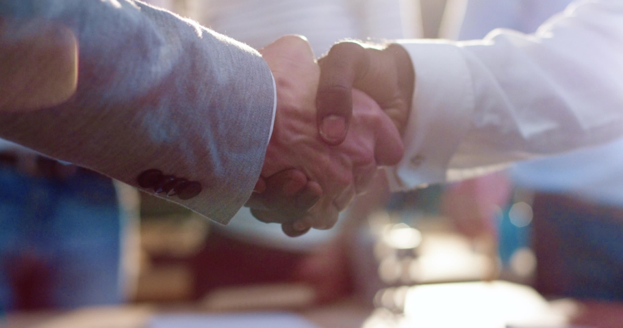 Close up of two men shaking hands. African American man holds out his hand to Caucasian man. Slow motion. Team ritual.