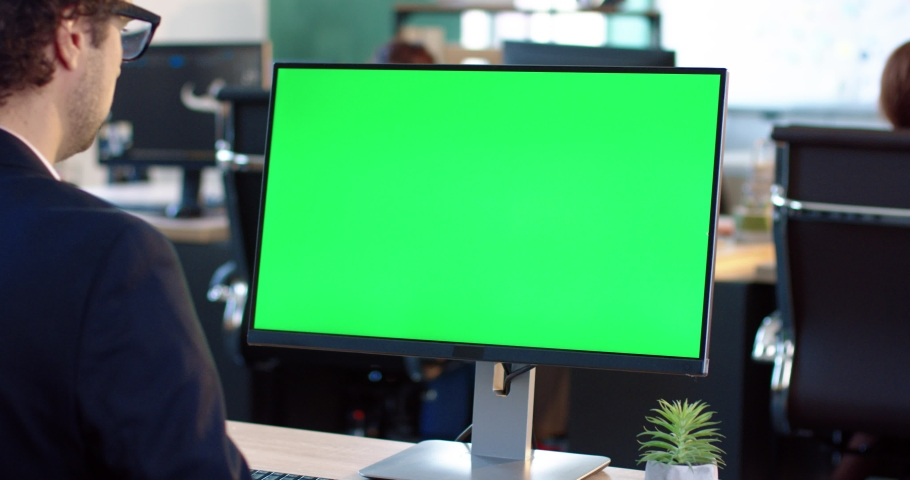 Close up of monitor in office. Green screen. Employee working at computer sitting at desk. View from back. Royalty-Free Stock Footage #1061189476