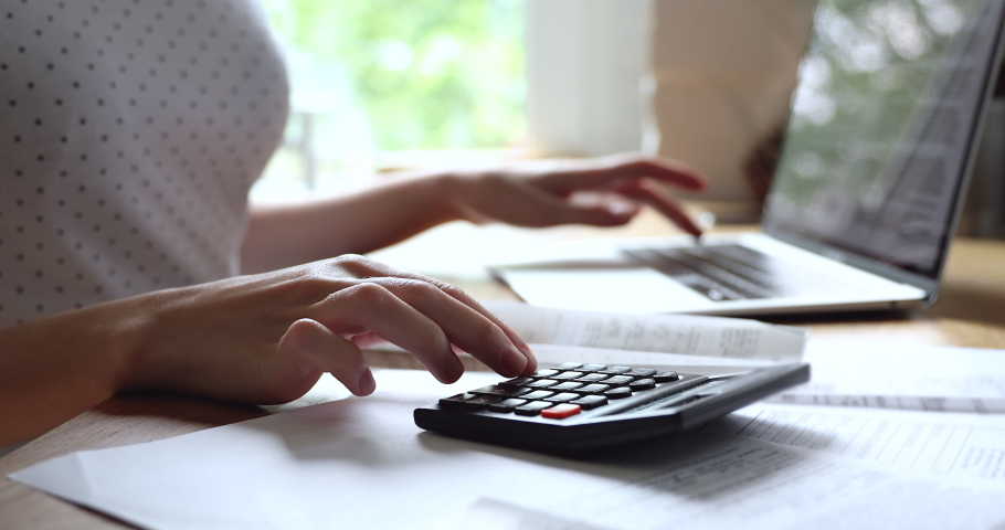 Close up young woman summarizing monthly incomes and outcomes with calculator, checking electronic bills in e-banking computer application, managing expenditures and household money payments. Royalty-Free Stock Footage #1061190646