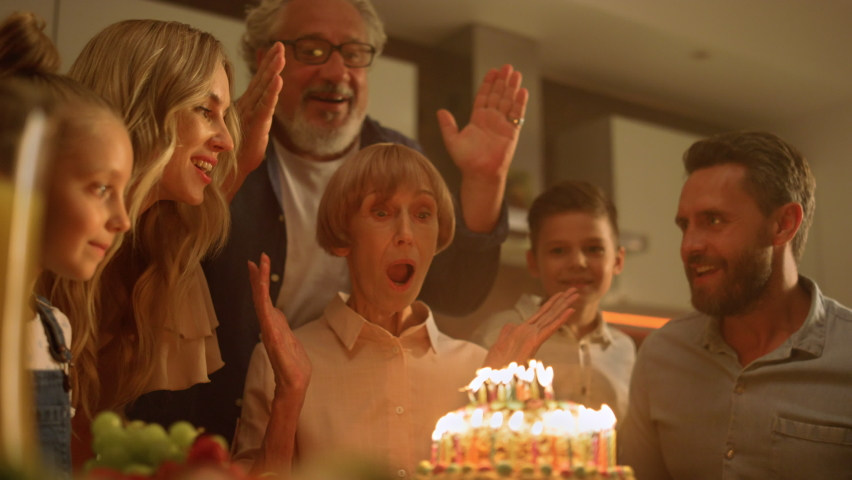 Big family celebrating grandmother birthday at home. Senior man closing woman eyes for surprise. Excited mature woman looking at cake with burning candles. Happy family clapping hands together Royalty-Free Stock Footage #1061190691
