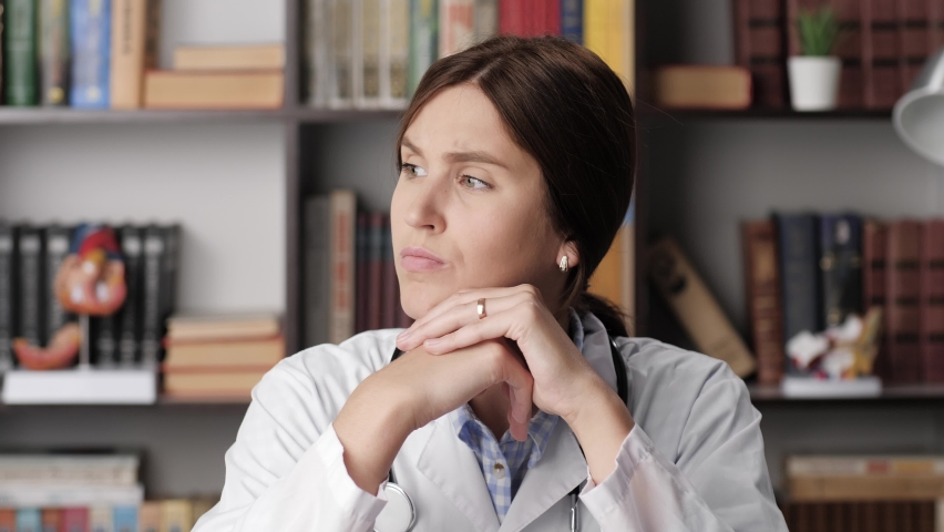 Doctor is thinking. Pensive woman doctor in white coat at workplace in hospital office sits with his hands folded on table and is thinking about something while looking out window Royalty-Free Stock Footage #1061193154