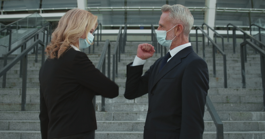 Male and female colleagues in protective masks doing elbow bump, epidemic safety Royalty-Free Stock Footage #1061200399