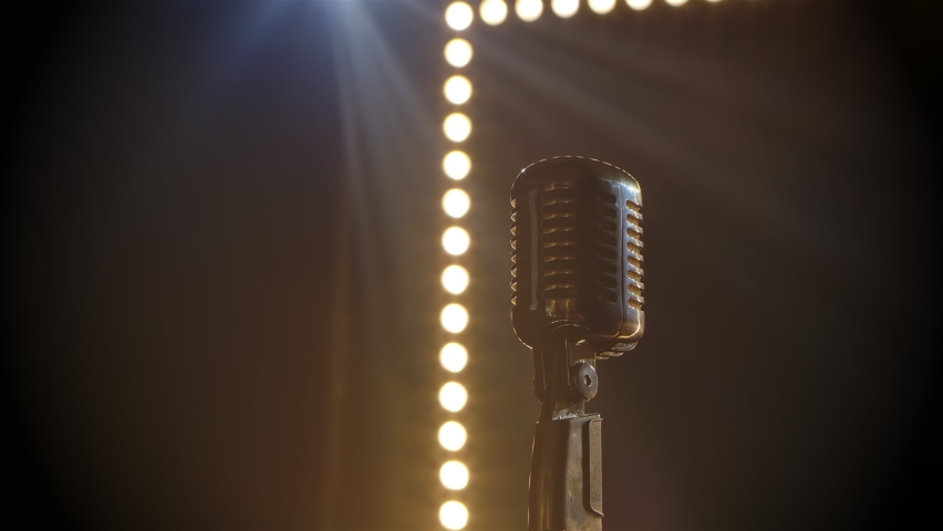 Microphone on stage with smoke anding light behind it. Professional concert vintage glare microphone for record or speak to audience on stage in empty retro club close up. | Shutterstock HD Video #1061201572