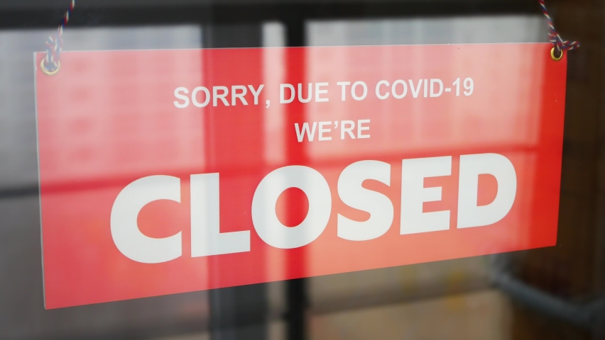A business owner changes the sign on the front door with the inscription OPEN to the CLOSED due to COVID-19 close-up