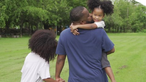 Happy mixed race family. African father carrying and holding hands his two little daughter walking together in the park. Dad and cute child girl kid enjoy and having fun outdoor weekend activity.