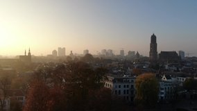 Cinematic 4k aerial video of historic Utrecht city center with the Dom Church with foggy golden light and fall colours