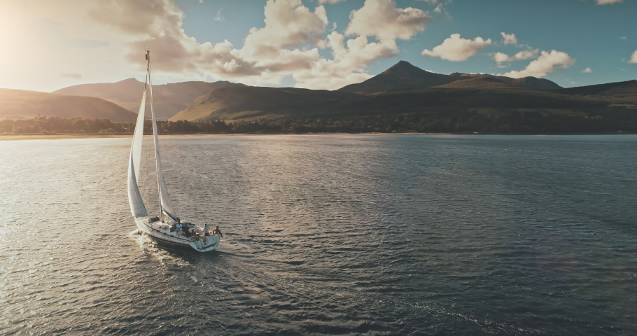Sailing yacht in wind waves at Arran Island sea bay in Scotland. Amazing seascape at Brodick port city. Lonely sail boar race at sun shine with fluffy clouds. Serene water scape and transportation Royalty-Free Stock Footage #1061205181