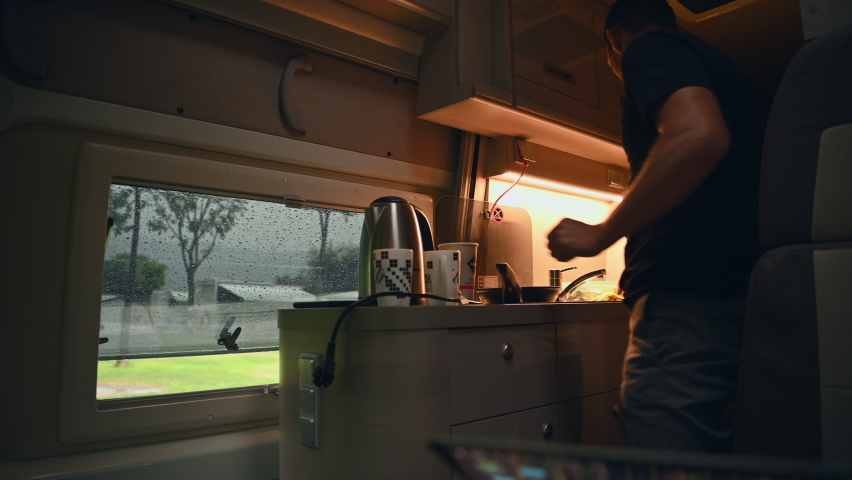 Caucasian Men in His 40s Preparing Hot Tea Inside His Motorhome Class B Camper. Rainy Day Outside During Camping. Royalty-Free Stock Footage #1061209627
