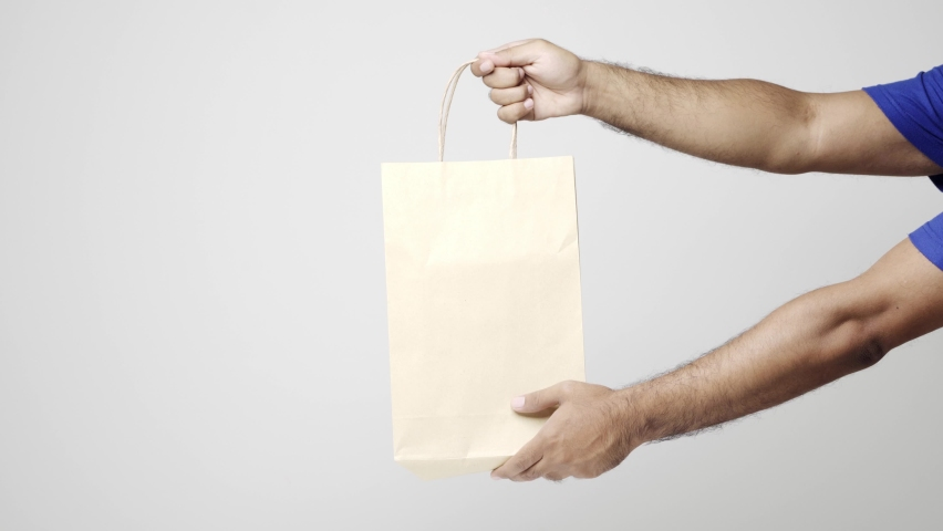 Close up hands delivery man sending the paper bag to customer on isolated white background. Logistic cargo shopping online concept. 4k resolution. | Shutterstock HD Video #1061215000