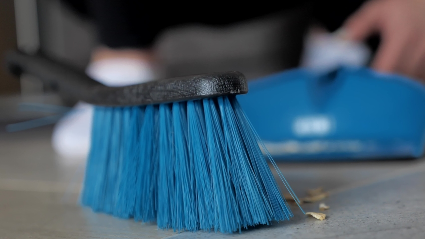 Extreme close up Female hand used brush up sweeping a dusty kitchenalong with the scoop in the morning Cleaning house concept. Slow motion. Low angle defocused view 4k | Shutterstock HD Video #1061217592