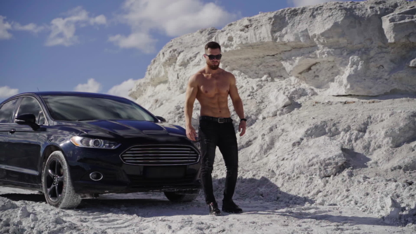 Handsome man near the black car. Shirtless guy in black sunglasses with sportive body walking in white mountains in a summer day. Slow motion.