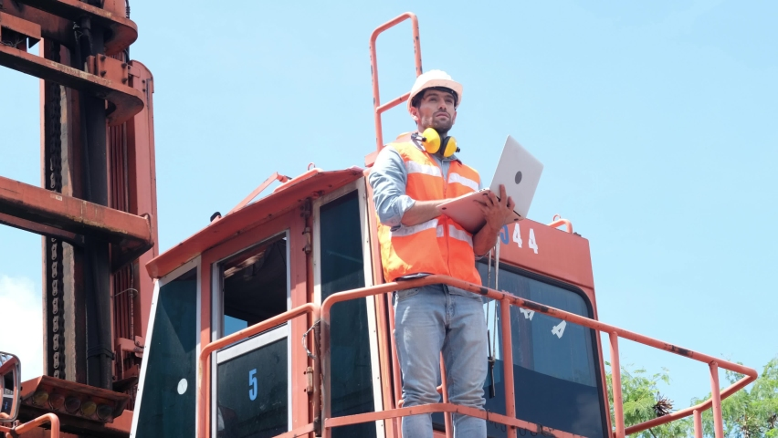 Engineer control loading Container on delivery truck with laptop in container yard area to Cargo freight ship for global import and export business , supporting logistics transportation concept. | Shutterstock HD Video #1061219980