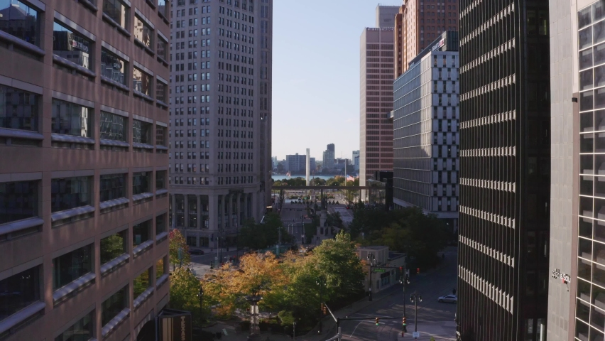Aerial Drone Flying Between Buildings Over Woodward Avenue Towards Windsor Detroit River in Motown Detroit Michigan on Sunny Morning, development of motor city