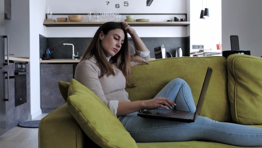 Young woman smilling sitting in cozy living room on green couch holding using laptop. Smiling casual lady chatting with friends, working or studying from home online on computer tech relaxing on sofa | Shutterstock HD Video #1061222569