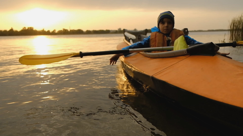 Evening kayak trip along the river in autumn. The active lifestyle of the child in the family. | Shutterstock HD Video #1061224018