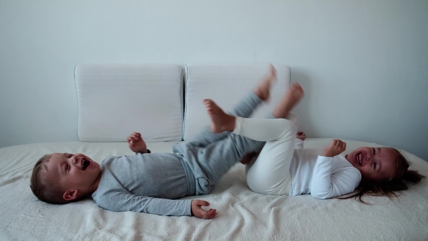 Family, innocence, infant concepts - Two smiling children do leg exercises laying on white bed. Siblings little boy and girl brother and sister have fun and laughing, happy kids on quarantine at home. | Shutterstock HD Video #1061229022
