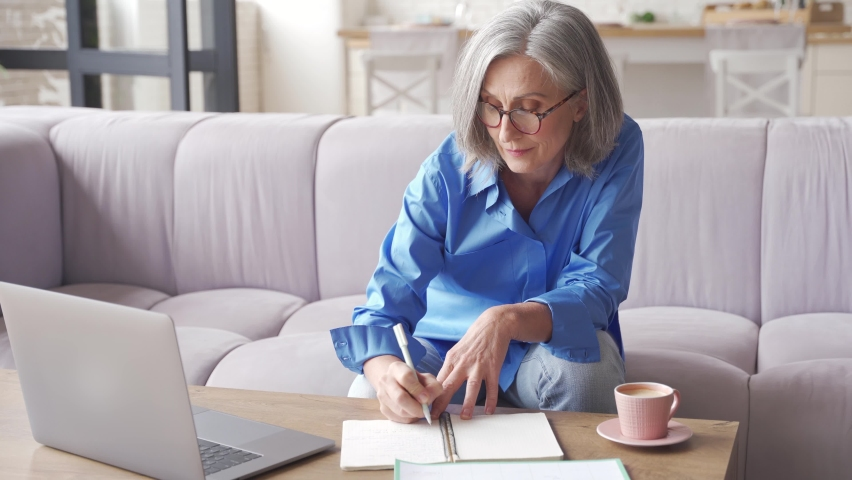 Senior mature older woman watching business training, online webinar on laptop computer remote working or social distance learning from home. 60s businesswoman video conference calling in virtual chat Royalty-Free Stock Footage #1061230510