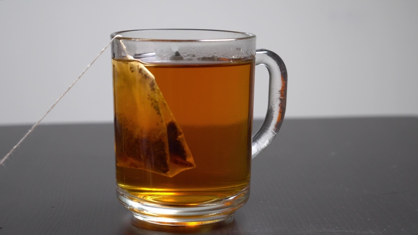 Boiling water is poured into a glass cup with a disposable tea bag on white bachground. Hot cup of black tea. | Shutterstock HD Video #1061231284