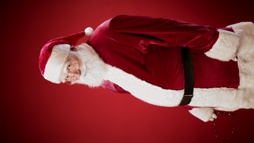 Vertical view shot of Santa Claus putting off glasses, putting on red sunglasses and making cool sign with his fingers while standing against red background | Shutterstock HD Video #1061231410