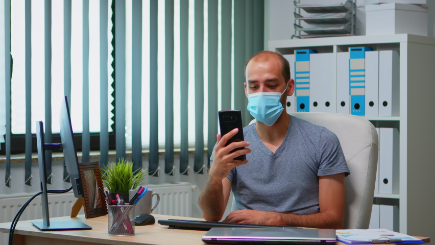 Man wearing protection face mask using smartphone webcam having virtual meeting. Freelancer working in new normal office workplace chatting talking having virtual conference, using internet technology | Shutterstock HD Video #1061232379