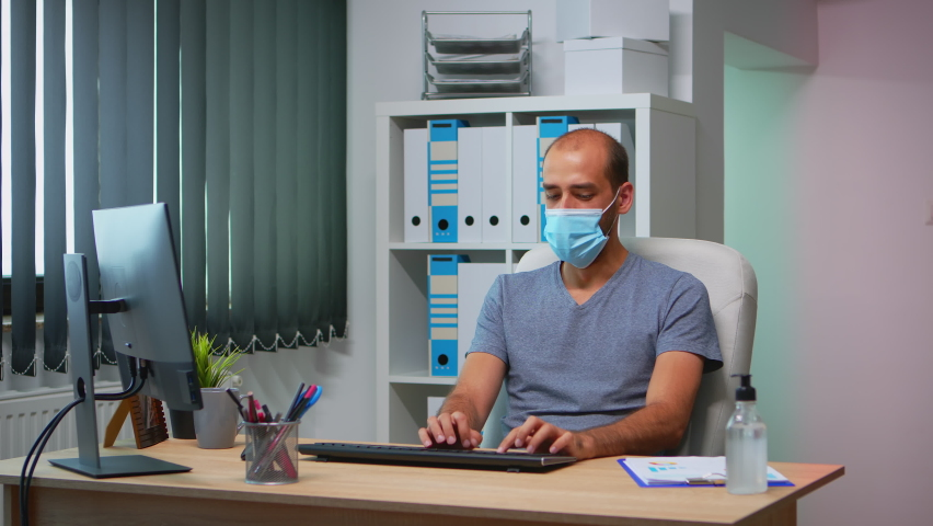 Coworkers with protection face masks working together in workplace during pandemic. Team in new normal office workspace in personal corporate company typing on computer keyboard looking at desktop | Shutterstock HD Video #1061232385