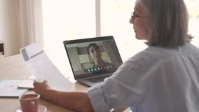 Senior woman recruiter talking to seeker during social distance job interview by video call. Elderly hr hiring female applicant communicating in conference virtual chat videocall meeting on laptop.