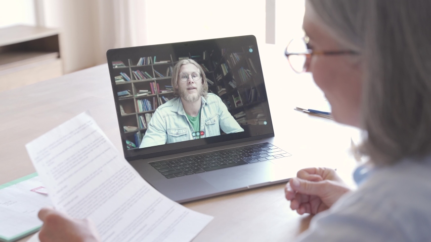 Senior business woman distance teacher giving online class for student. Business woman talking with client, colleague, in video conference call virtual chat meeting on laptop working from home office.