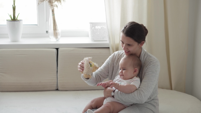 Medicine, healthcare, family, innocence, pediatrics, happiness, infant concepts - Young happy mother read book and play with chubby 7 month baby sitting in bright sunlight nursery on soft white bed. | Shutterstock HD Video #1061232571