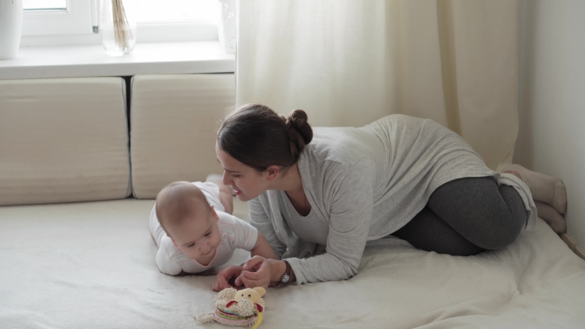 Medicine, healthcare, family, innocence, pediatrics, happiness, infant concepts - Young happy mother read book and play with chubby 7 month baby sitting in bright sunlight nursery on soft white bed. | Shutterstock HD Video #1061232574