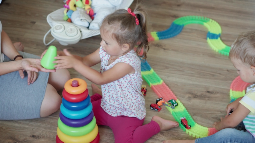 Childhood, games, upbringing and development concept - top view of mom with newborn baby and children boy and girl sister play with magic road in kid playroom. Siblings have fun at home on quarantine | Shutterstock HD Video #1061232586