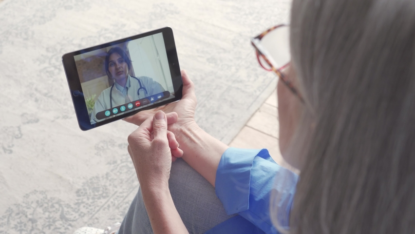 Over shoulder view of older elderly woman patient meeting virtual doctor using tablet at home. Online telemedicine visit. Seniors ehealth, telehealth medical consultation, tele medicine video call.