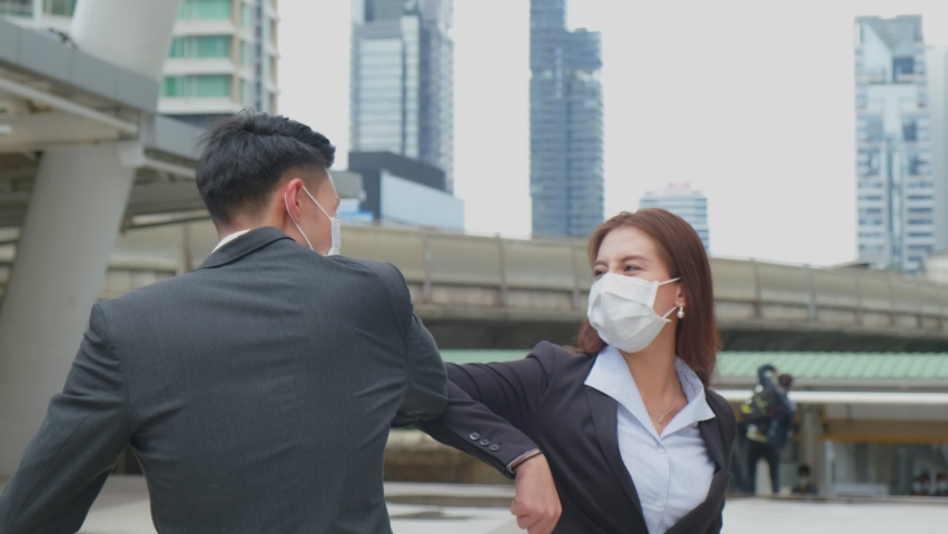 Asian business people wearing protective face mask outside in city due to COVID pandemic crisis. Male and female engineers making elbow touch instead of handshake to avoid coronavirus infection. Royalty-Free Stock Footage #1061233897