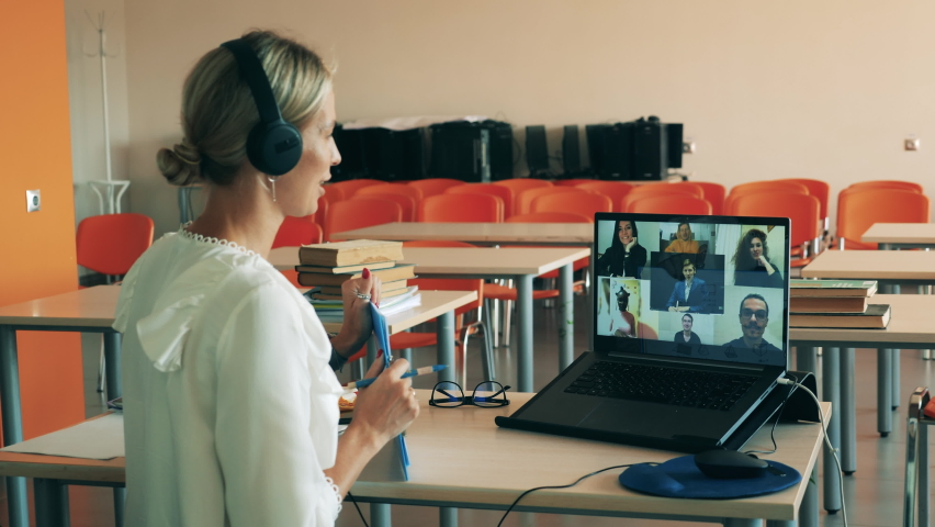 A woman is talking to multiple users during a virtual lesson. Remote education, online college lesson, distant studying concept. Royalty-Free Stock Footage #1061233999
