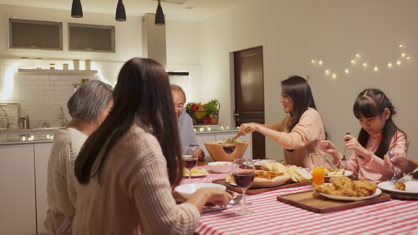 Happy family time and relationship, Asian big family having small party eating food together at home. Grandparent is happy to see his child and nephew eating and sharing food on dining table at home. | Shutterstock HD Video #1061234329