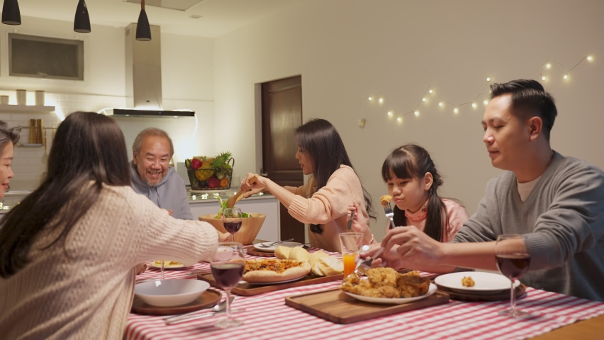 Happy family time and relationship, Asian big family having small party eating food together at home. Grandparent is happy to see his child and nephew eating and sharing food on dining table at home. Royalty-Free Stock Footage #1061234329