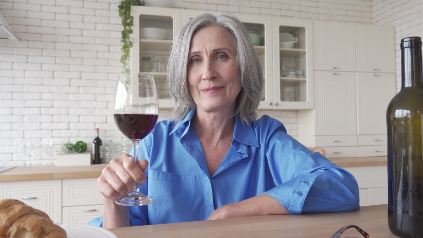 Happy senior woman drinking wine video calling friend at home. Old lady holding glass talking to web cam by online social distance holiday party family chat meeting sit at kitchen table. Webcam view. | Shutterstock HD Video #1061234476