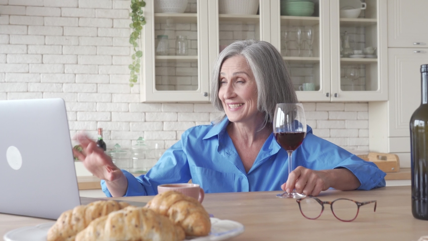 Happy senior woman drinking wine video calling friend on holiday party on laptop at home. Smiling old middle aged lady holding glass talking in online social distance chat sitting at kitchen table. | Shutterstock HD Video #1061234479