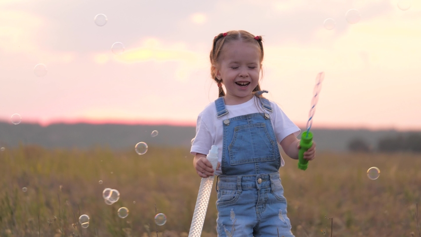 Healthy child is playing in park with soap bubbles. baby rejoices in air bubbles. daughter plays in park at sunset. Happy family and childhood concept. soap bubbles on field, children's birthday | Shutterstock HD Video #1061235913